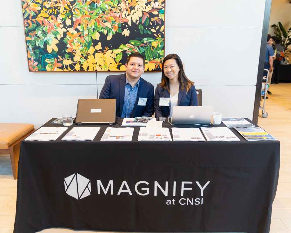 A smiling man and woman seated at the Magnify at CNSI Exhibitor Table