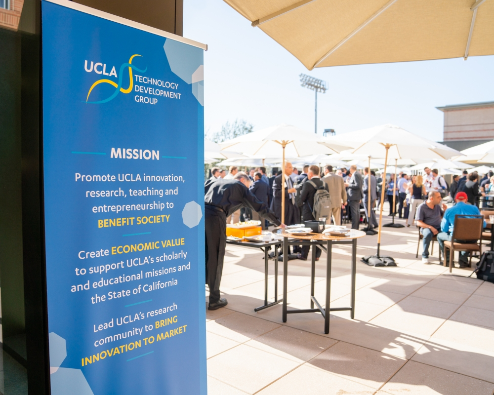 A crowd of attendees on an outdoor terrace under shade umbrellas, with a UCLA sign in the foreground