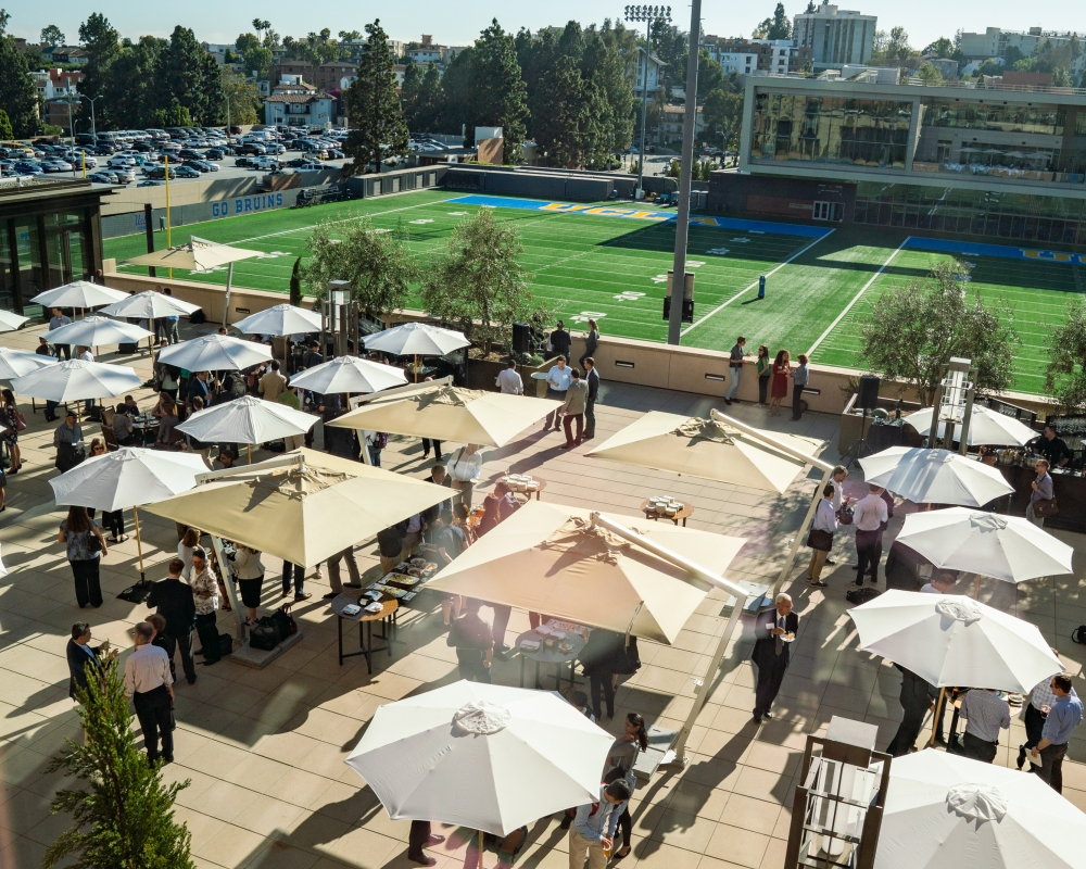 Overhead view of a sunny outdoor terrace with several shade umbrellas and a crowd of attendees networking